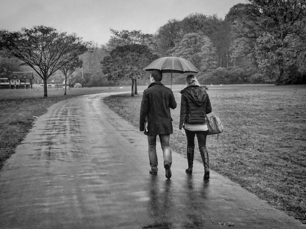 man-en-vrouw-onder-paraplu-lopen